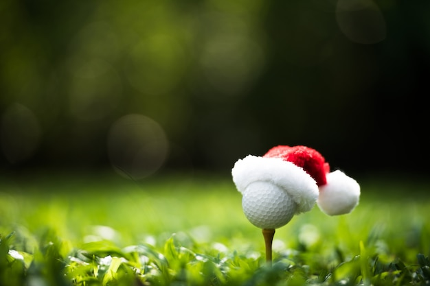 Festive-looking golf ball on tee with santa claus' hat on top for holiday season on golf course