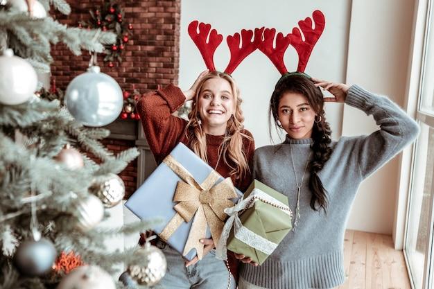 축제 매너. 크리스마스 트리 근처에 서있는 동안 축제 사슴 귀와 장식 선물을 보여주는 매력적인 장발 소녀