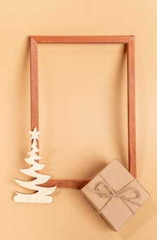 Festive minimal layout with empty wooden frame, small wooden carved decoration - xmas tree, cardboard gift box on beige background. christmas or new year mock up. top view. copy space. vertical photo.
