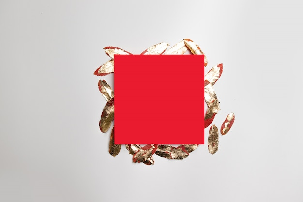 Festive minimalistic concept of red square frame template with gold leaves on gray background.