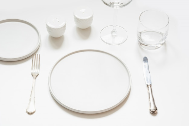 Festive modern white table setting. plates and cutlery on white.