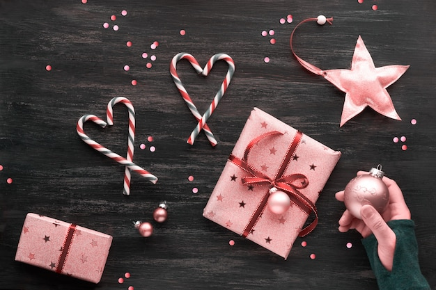 Festive monochrome pink christmas background with pink gift boxes, stripy candy canes, trinkets, stars and confetti. geometric creative flat lay with copy-space