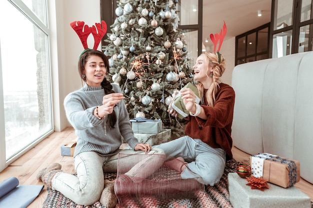 축제 분위기. 장식 된 크리스마스 트리 근처에서 놀면서 스웨터와 청바지를 입고 행복한 웃음 장발 숙녀
