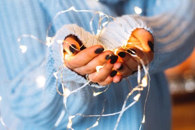 축제 분위기. 겨울 휴가 실내 장식. 여자 손에 하얀 요정 조명의 근접 촬영입니다.
