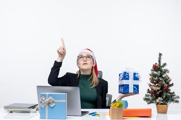Atmosfera festosa con curiosa giovane donna positiva con cappello di babbo natale e occhiali da vista seduto a un tavolo che mostra il regalo di natale rivolto sopra su sfondo bianco