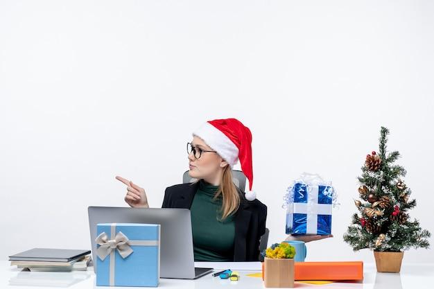 Umore festivo con la giovane donna sorpresa curiosa con il cappello di babbo natale e gli occhiali da portare seduti a un tavolo che mostra il regalo di natale che punta qualcosa sul lato destro su priorità bassa bianca