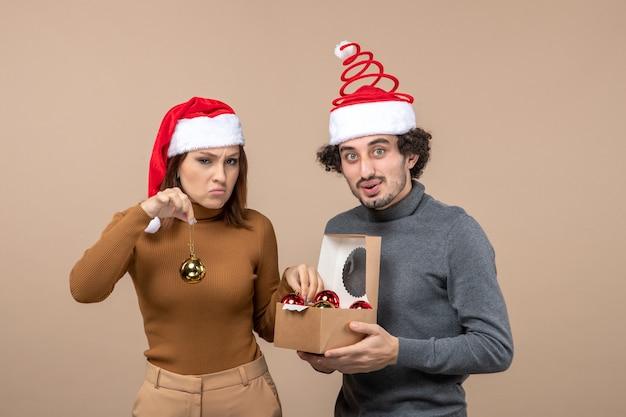 Umore festivo con coppia adorabile divertente eccitata che indossa cappelli rossi di babbo natale su metraggio grigio
