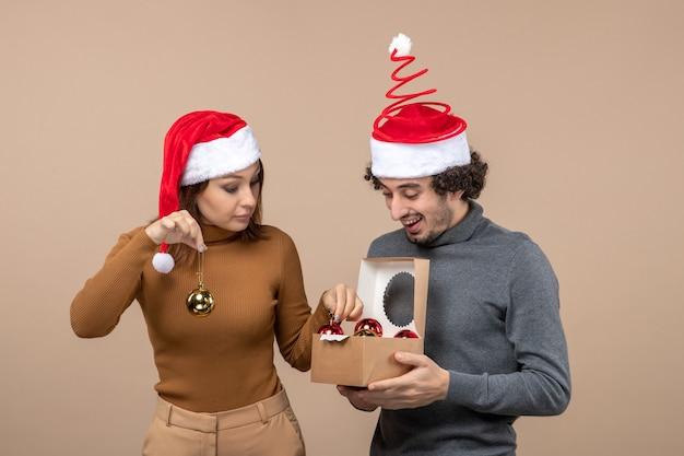 Stato d'animo festivo con coppia adorabile eccitata che indossa cappelli rossi di babbo natale su metraggio grigio