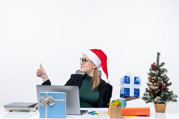 Праздничное настроение с удивленной молодой женщиной в шляпе санта-клауса и очках, сидящей за столом, показывая рождественский подарок, указывая на что-то с правой стороны, делая жест