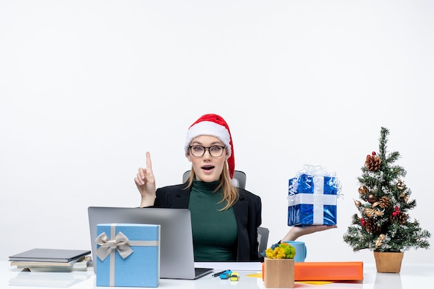 Праздничное настроение с удивленной молодой женщиной в шляпе санта-клауса и в очках, сидящей за столом, показывающим рождественский подарок, указывающим выше на белом фоне