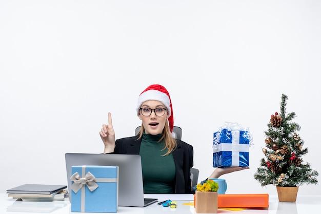 Atmosfera festosa con giovane donna sorpresa con cappello di babbo natale e occhiali da vista seduto a un tavolo che mostra il regalo di natale rivolto sopra su sfondo bianco