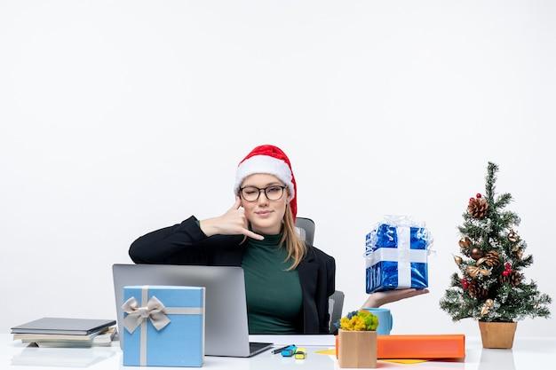 Umore festivo con la giovane donna con il cappello di babbo natale e gli occhiali da portare seduti a un tavolo che mostra il regalo di natale facendo mi chiama gesto su sfondo bianco
