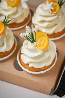 クリームチーズクリームと柑橘系のフィリングが入ったお祭りマフィン。休日の菓子。キンカン、ローズマリー、マスチックな雪片で飾られたデザートがギフトボックスに詰められています。