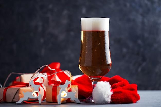 Праздничный новогодний и рождественский бокал светлого пива на столе с копией пространства для подарков