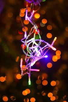 야외 장식된 전나무 나뭇가지에 흐릿한 화려한 조명이 있는 축제 새해 배경.