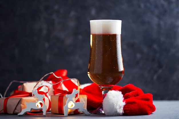Festive new year and christmas glass of light beer on the table with gifts copy space