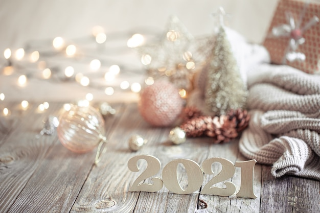 Festive new year composition with wooden new year number on a light blurred background with christmas decoration.