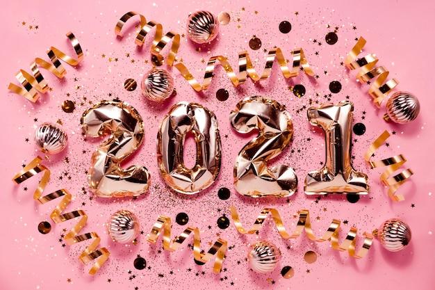 お祝いの新年flatlay背景ピンクゴールドホイル風船とchrtistmas装飾。上部の水平ビューのコピースペース。