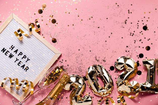 Праздничные новогодние шары из фольги из розового золота и рождественские украшения. горизонтальный вид сверху copyspace.