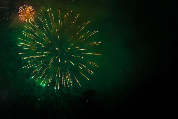 Праздничный новогодний салют в темном небе. яркие огни сверкают