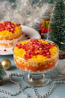 Festive new year's salad with chicken, eggs, carrots and corn, decorated with a star of pomegranate seeds