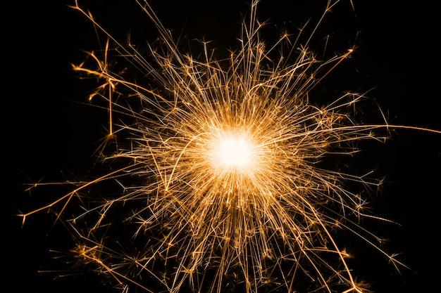 お祝いの新年の単色の輝く燃える線香花火または黒い背景に敬礼。休日のコンセプト、背景、コピースペース。