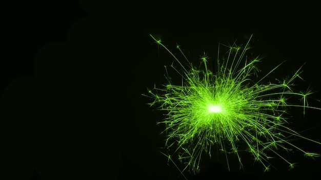Festive new year's single green sparkling burning sparkler or salute on a black background. holiday concept, background, copy space.