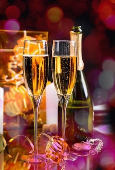 お祝いの新年の静物-光沢のある背景にボトル、懐中時計、ゴールドラップギフト付きのスパークリングシャンパン2杯