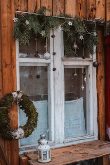 Festive new year window decoration with fir branches, garlands and cones. merry christmas sign and baubles on the window sill