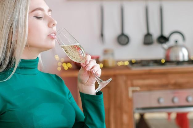 Праздник. портрет крупного плана белокурой дамы, пьющей шампанское на кухне.
