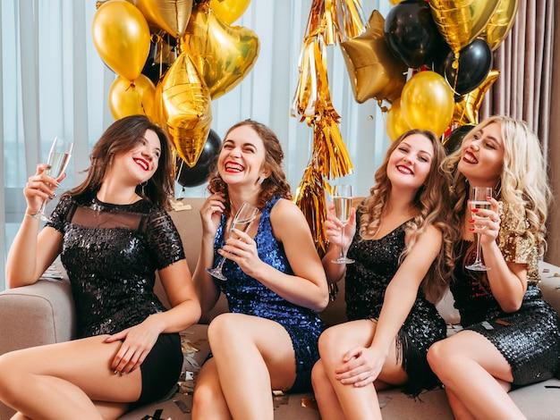 お祝いの機会。ぶらぶらしている女性、スパークリングワインを飲んでいる女性、豪華なパーティーでエンターテイメントを楽しんでいる女性。