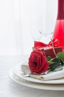 赤いバラとお祝いまたはロマンチックなディナー。バレンタインデー。