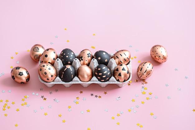 Festive uova di pasqua dipinte sulla superficie rosa.