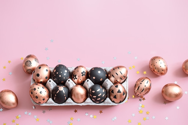 Festive painted in gold and black easter eggs on pink.