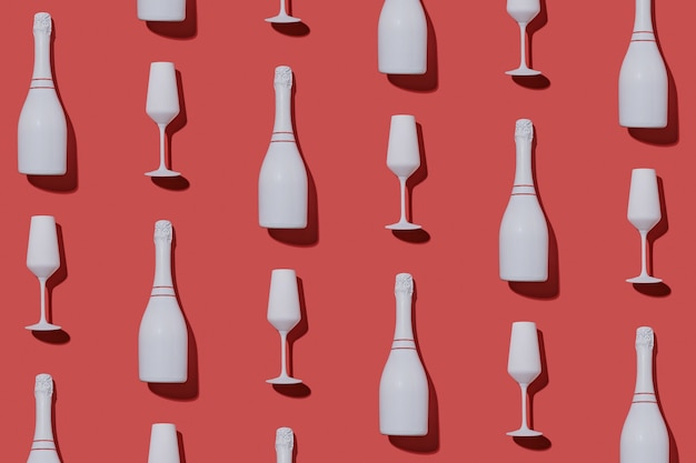 Festive party background with champagne bottles and flutes arranged in an alternating flat lay pattern on red for valentines, romance, new year and christmas themes