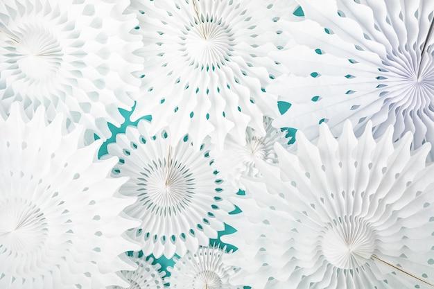 青いパステルカラーの背景の上に白い紙のサークルファンとお祝いパーティーの背景。お祭り、誕生日、ベビーシャワー、結婚式の装飾。上面図