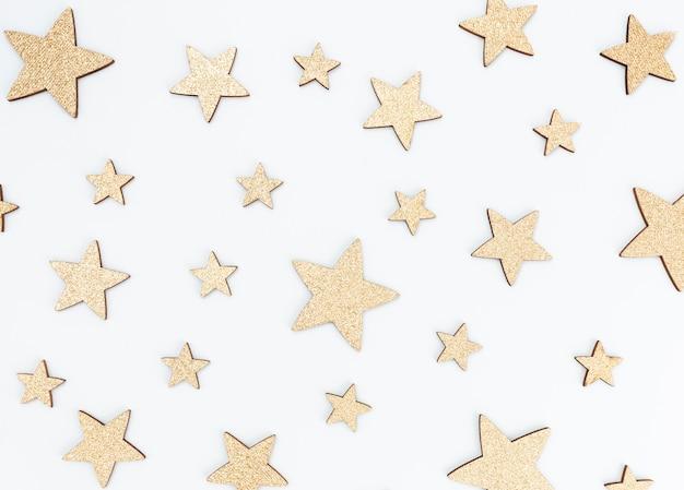 Праздничный пастельный фон. рождественские звезды и сияющий блеск, конфетти на пастельном фоне. новогодний фон, плоская планировка.