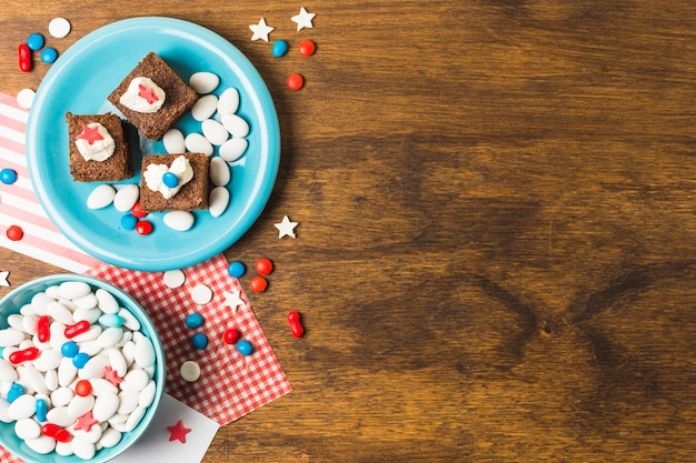 Festive patriotic cakes with candies for independence day on wooden table