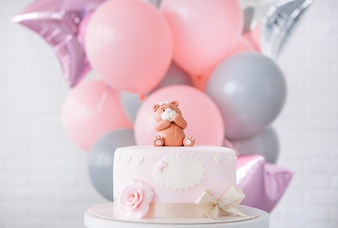 Festive pink cake with a bow and a bear on top of a background of balloons