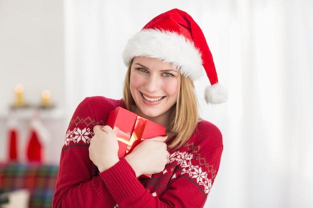 Festive pretty woman hugging her gift