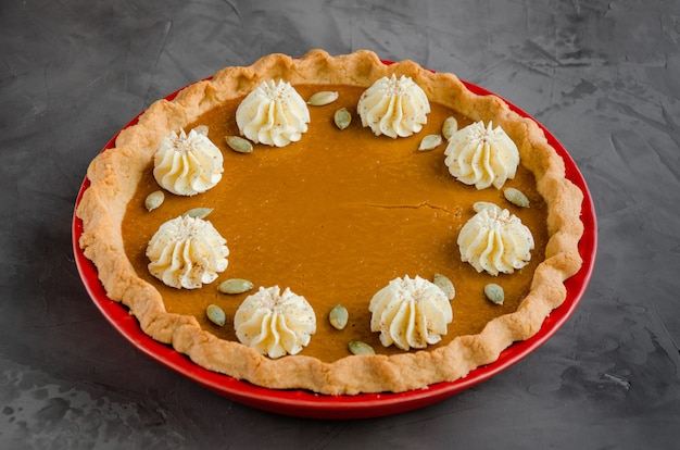 Festive pumpkin pie with spices, whipped cream and seeds