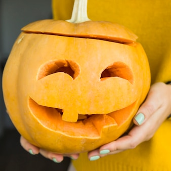 A festive pumpkin with eyes carved and a mouth with a candle inside