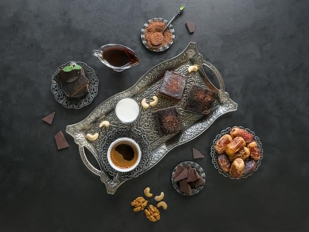 お祝いラマダンの背景。日付のあるブラウニー、ダークチョコレート、牛乳、コーヒーが黒い表面に配置されています。