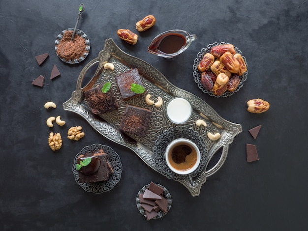 Festive ramadan. brownies with dates, milk and coffee are laid out on a black surface.