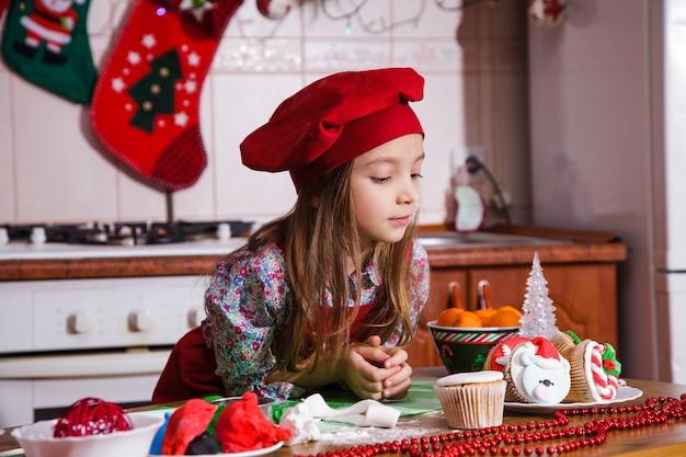 お祝いの赤いエプロンクリスマスパーティーディナーデザートペパーミントカップケーキチーズクリームシュガー振りかける装飾