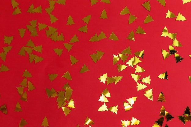 Праздничный красный фон сияющее золотое конфетти в виде новогодней елки рождество и новый год