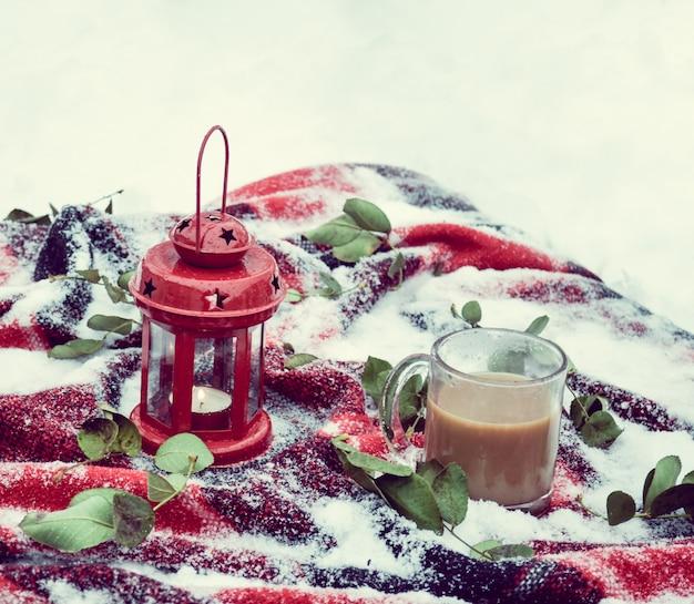 랜턴에 축제 붉은 촛불과 눈이 깔린 깔개에 커피 한 잔