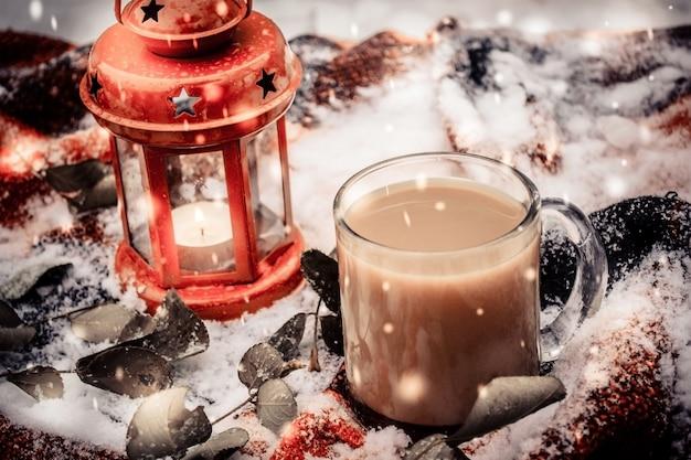 Праздничная красная свеча в фонаре и кружка кофе на коврике со снегом