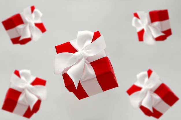 Festive red gift boxes with white bows levitating isolated on a gray background