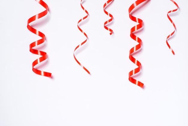 白い背景で隔離のお祝いの赤いリボン